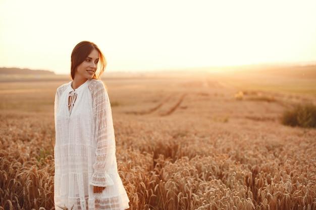Linda garota com um vestido branco. mulher em um campo de trigo de outono.