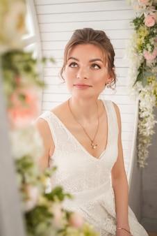Linda garota com um vestido de noiva branco sentada em uma janela redonda
