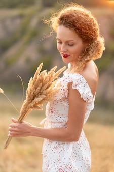 Linda garota com um vestido de verão branco caminha ao pôr do sol em um campo com um buquê de espigas