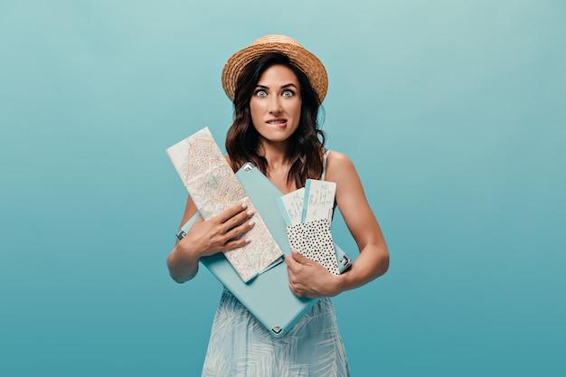 Linda garota com um vestido de verão elegante detém cartão, mala e ingressos sobre fundo azul. morena com chapéu de palha morde o lábio e posa para a câmera.