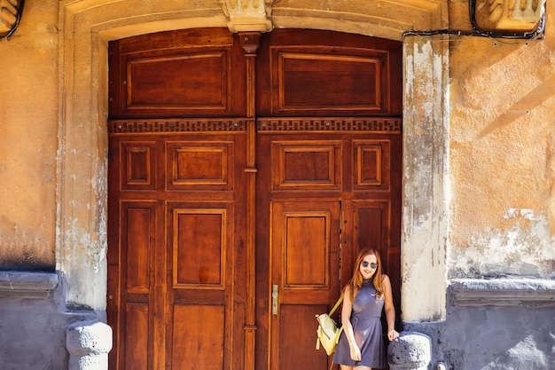 Linda garota com um vestido e uma mochila nos ombros em pé perto de um antigo prédio com porta de madeira