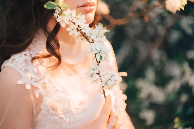 Linda garota com um vestido leve com um jardim florido. fechar-se