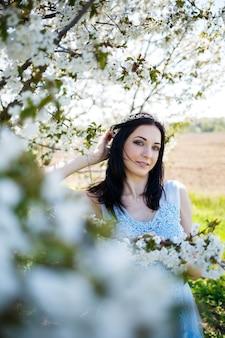 Linda garota com um vestido longo azul verão claro adornado no cabelo contra uma árvore em flor. retrato carinhoso de uma jovem em flor branca