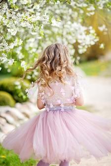 Linda garota com um vestido rosa no jardim com cerejeiras em flor. linda garota se divertindo e curtindo