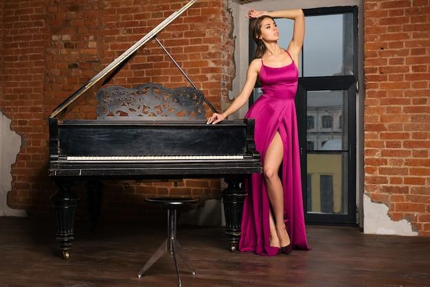Linda garota com um vestido vermelho clássico longo posando com um piano velho