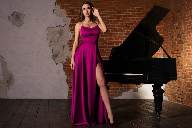 Linda garota com um vestido vermelho clássico longo posando com uma imagem de piano antigo
