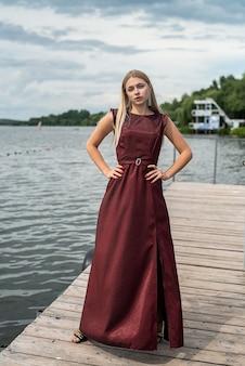 Linda garota com um vestido vermelho escuro muito elegante perto da lagoa no parque sity.