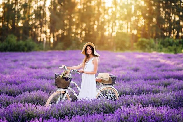 Linda garota com uma bicicleta em um campo de lavanda. linda garota em fundo roxo.