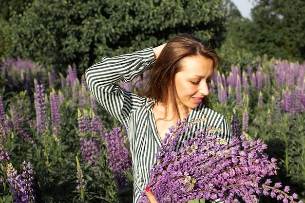 Linda garota com uma blusa listrada posando com uma braçada de tremoço em um prado florido