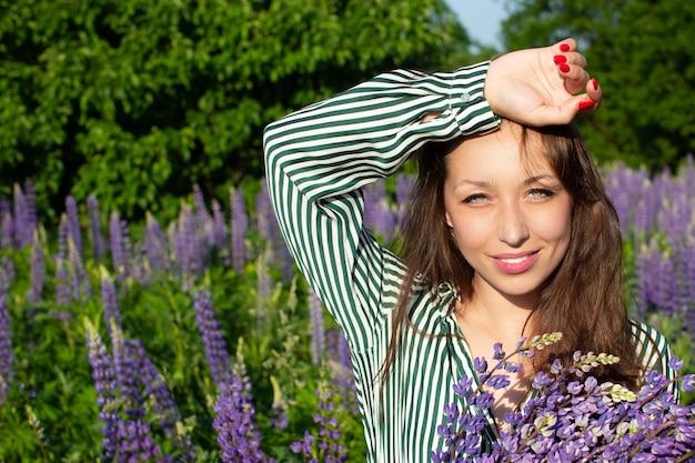 Linda garota com uma blusa listrada, posando com uma braçada de tremoço no campo
