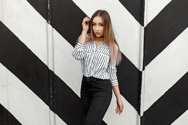 Linda garota com uma blusa na moda perto do desenho da parede com linhas