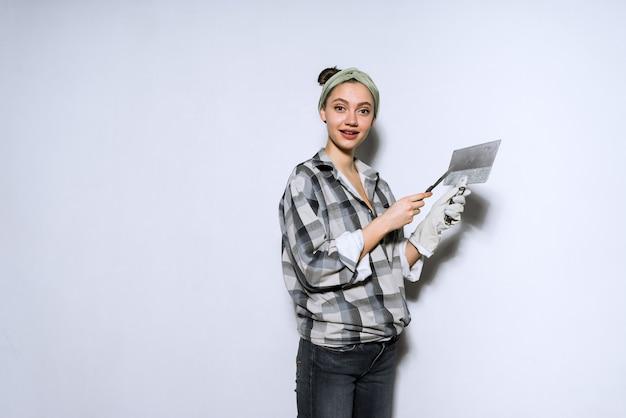 Linda garota com uma camisa quadriculada fazendo reparos, nivelando paredes com uma espátula