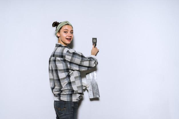 Linda garota com uma camisa xadrez fazendo reparos em seu apartamento, nivelando as paredes com uma espátula