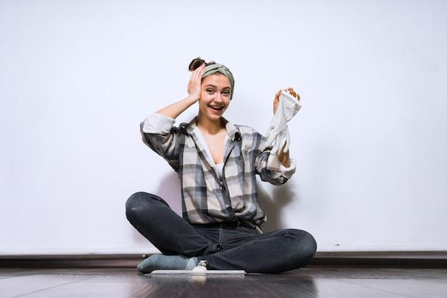 Linda garota com uma camisa xadrez sentada no chão, segurando uma luva de borracha, fazendo reparos