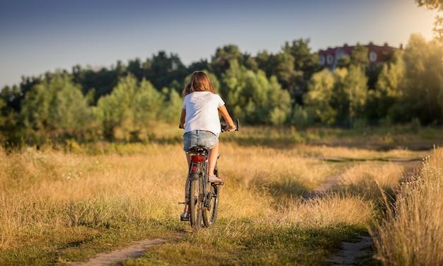 Linda garota com uma camiseta andando de bicicleta em um prado ao pôr do sol