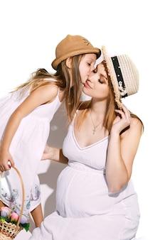 Linda garota com uma cesta de flores, inclinando-se para a mãe e beijando sua bochecha.