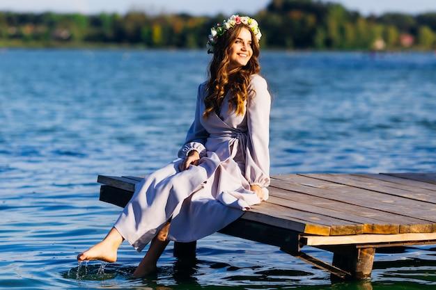 Linda garota com uma coroa na cabeça, sentado em um píer de madeira e molhar as pernas na água