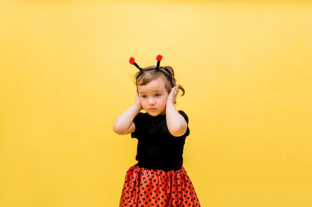 Linda garota com uma fantasia de joaninha cobriu seus ouvidos contra um amarelo isolado
