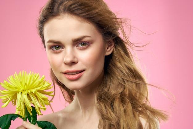 Linda garota com uma flor amarela em uma maquiagem de ombros nus de fundo rosa. foto de alta qualidade
