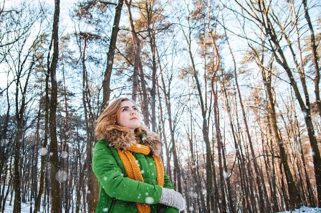 Linda garota com uma jaqueta de inverno e luvas em um fundo de floresta