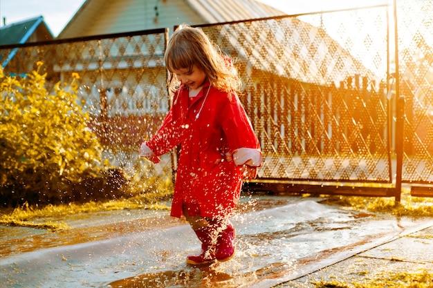 Linda garota com uma jaqueta vermelha está pulando na poça. o sol quente de verão ou outono de configuração. verão na aldeia.
