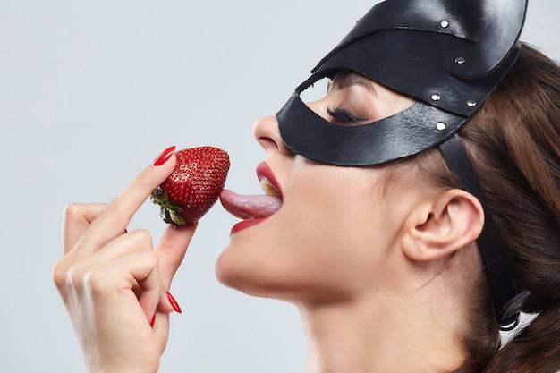 Linda garota com uma máscara de gato. sedutoramente posando com morangos