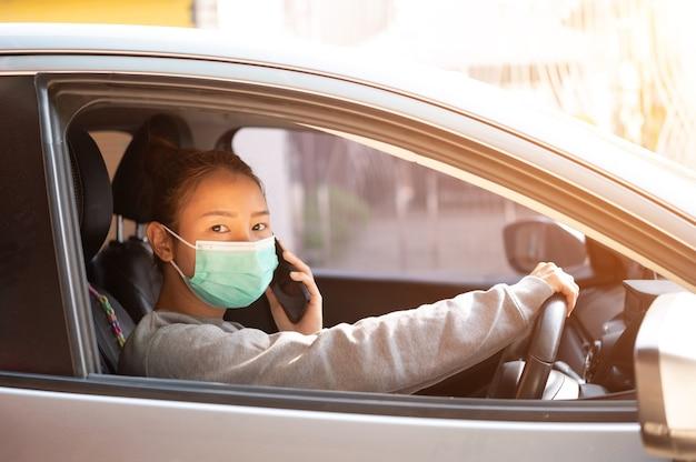 Linda garota com uma máscara, sentada em um carro,