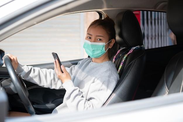Linda garota com uma máscara, sentada em um carro, Foto Premium