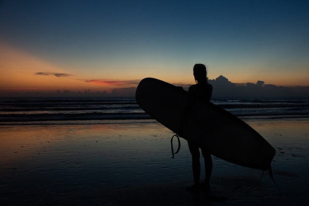 Linda garota com uma prancha de surf ao pôr do sol