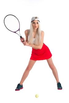 Linda garota com uma saia vermelha e um boné de beisebol segurando uma raquete de tênis