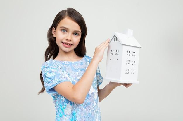 Linda garota com uma simulação de uma casa nas mãos de uma parede branca. a propriedade