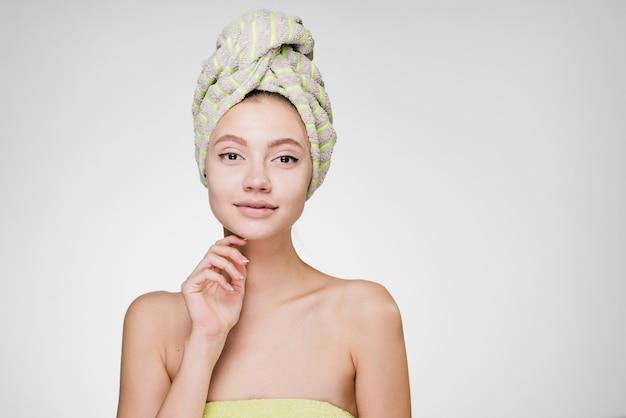 Linda garota com uma toalha na cabeça, curtindo um spa