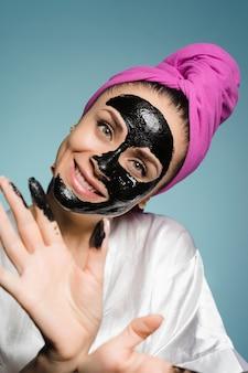 Linda garota com uma toalha rosa na cabeça aplicando uma máscara de limpeza preta no rosto, sorrindo