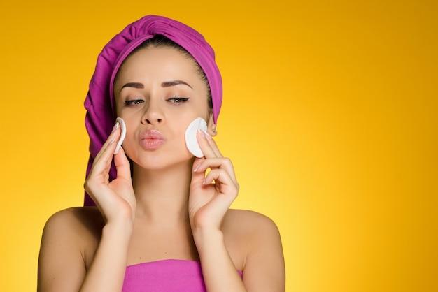 Linda garota com uma toalha rosa na cabeça e limpa o rosto com almofadas de algodão