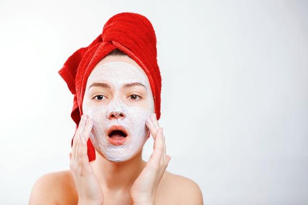 Linda garota com uma toalha vermelha na cabeça aplica uma esfoliação no rosto de um grande retrato em um branco