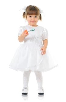 Linda garota com vestido branco festivo tem bolhas de sabão nas mãos. criança desvia o olhar, fundo claro