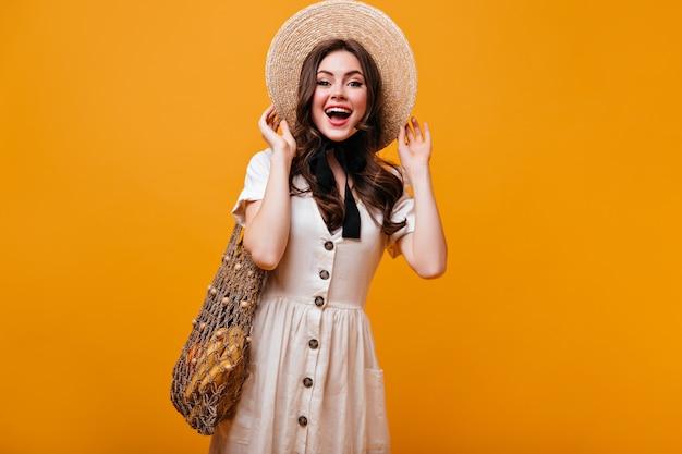Linda garota com vestido de algodão posando com saco de barbante com frutas. mulher com chapéu de palha com laço está rindo em fundo laranja.