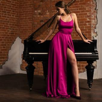 Linda garota com vestido vermelho longo clássico posando com piano velho.