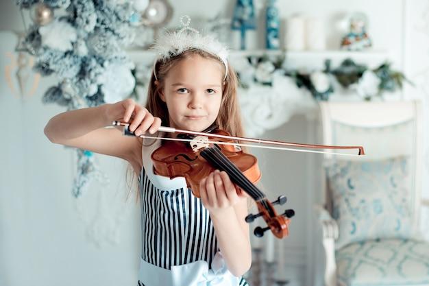 Linda garota com violino na sala de decoração de natal.