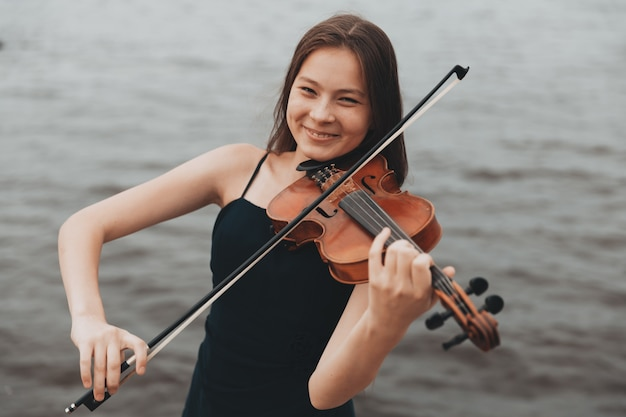 Linda garota com violino sorrindo na natureza. foto de alta qualidade