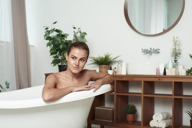 Linda garota com vitiligo está deitada na banheira, sorrindo para a câmera. fechar-se. conteúdo bela jovem relaxando enquanto toma banho.