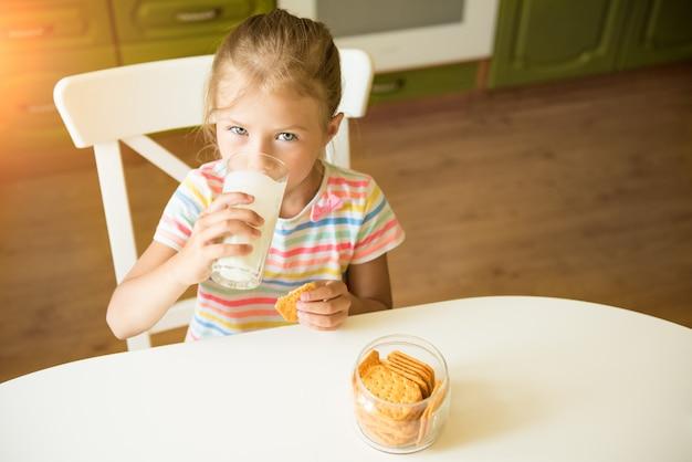 Linda garota come biscoitos e bebe leite sentado na cozinha