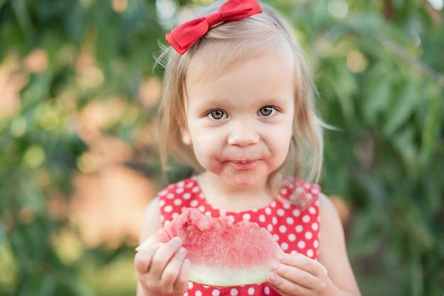 Linda garota come melancia suculenta na grama no verão
