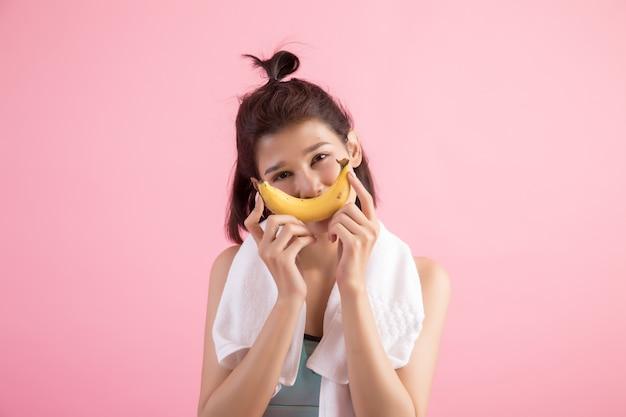 Linda garota comendo banana após o exercício para controlar o peso