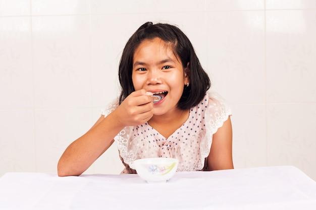 Linda garota comendo cereal matinal