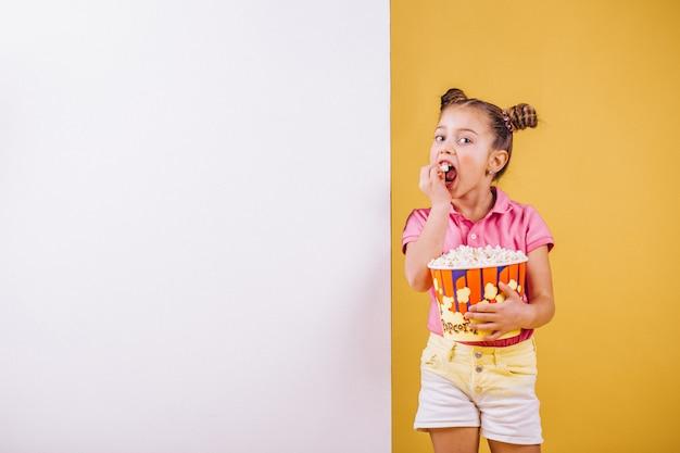Linda garota comendo pipoca