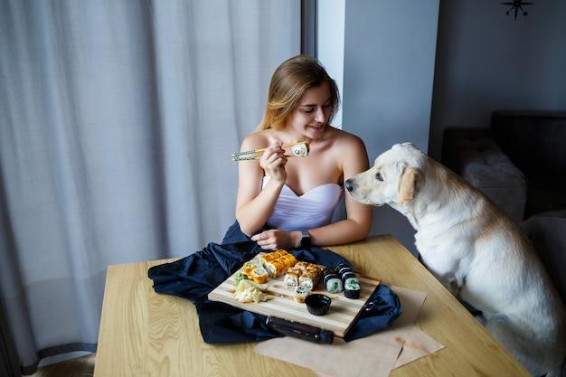 Linda garota comendo sushi close-up com seu cachorro labrador, sorrindo, segurando um rolo de sushi com pauzinhos. comida japonesa saudável.