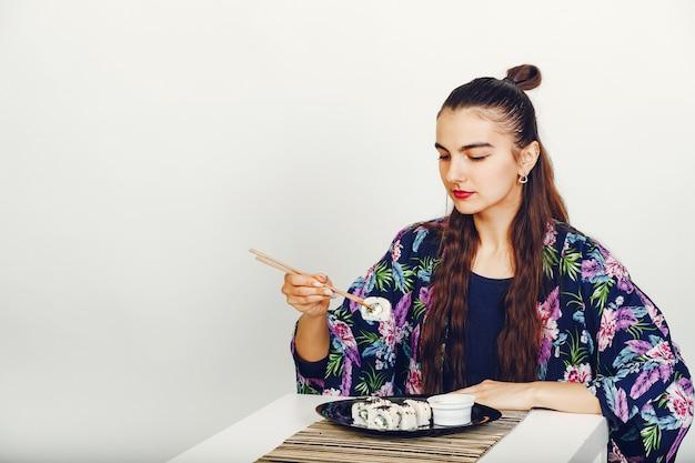 Linda garota comendo um sushi em um estúdio