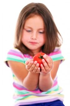 Linda garota comendo um tomate
