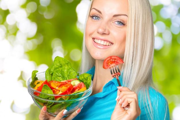 Linda garota comendo uma salada